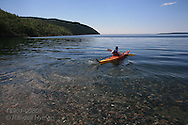 Man in kayak paddles across placid, crystalline waters of Lake Superior at Terrace Bay, Ontario; Canada.