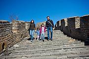 American Chinese family walk the ancient Great Wall of China at Mutianyu, north of Beijing, China