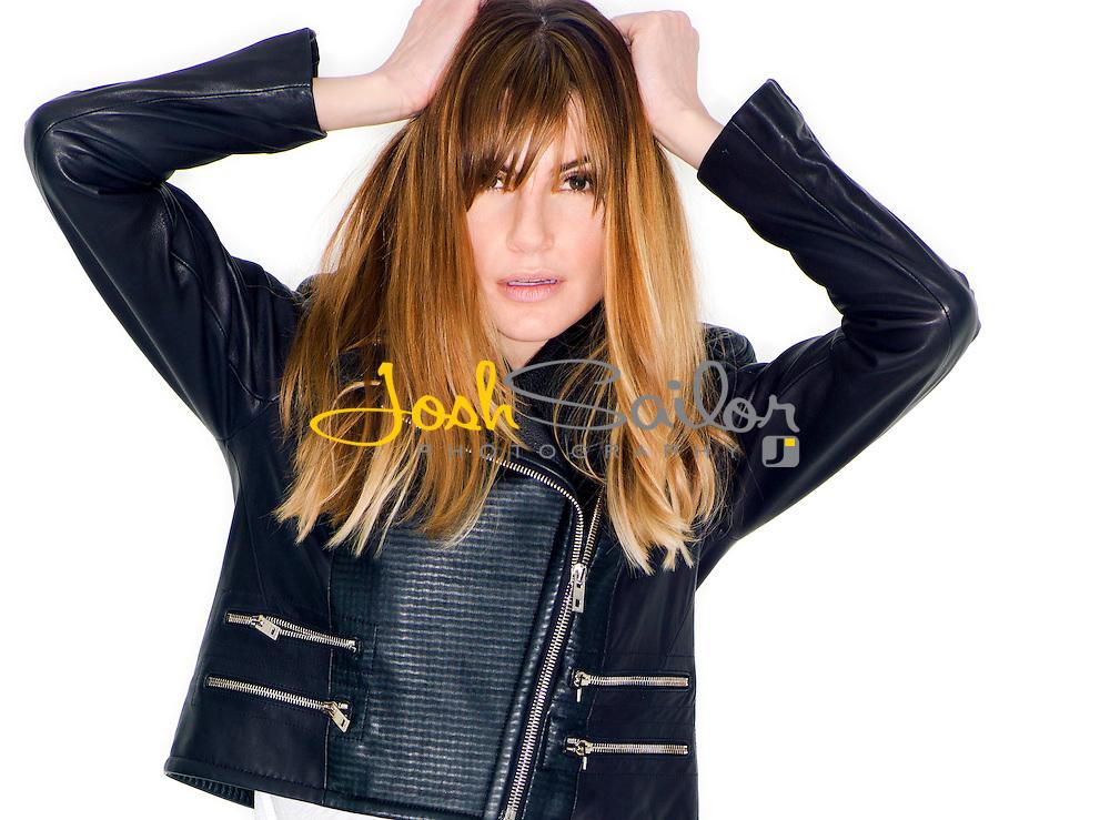 Beauty-shot of model Courtney, wearing a black leather jacket on white background.