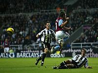 Photo: Andrew Unwin.<br />Newcastle Utd v Aston Villa. The Barclays Premiership.<br />03/12/2005.<br />Newcastle's Robbie Elliott (R) slides in to dispossess Aston Villa's Lee Hendrie (C).