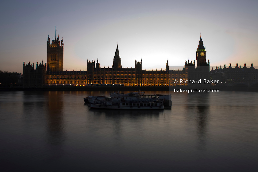 The tower containing Big Ben amid the Gothic architecture of Britain's Houses of Parliament seen from the Embankment at sunset.