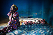 A Ghanaian woman sits on the floor of her bedroom - a dark, empty room devoid of any belongings and only a sheet on the ground for a bed. <br />