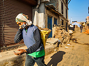 02 MARCH 2017 - SANKHU, NEPAL: Laborers carry dirt away from a home destroyed in the 2015 earthquake and still being dug out in Sankhu. Almost all of the work is being done by hand. There is more construction and rebuilding going on in Sankhu, west of central Kathmandu, than in many other parts of the Kathmandu Valley nearly two years after the earthquake of 25 April 2015 that devastated Nepal. In some villages in the Kathmandu valley workers are working by hand to remove ruble and dig out destroyed buildings. About 9,000 people were killed and another 22,000 injured by the earthquake. The epicenter of the earthquake was east of the Gorka district.   PHOTO BY JACK KURTZ