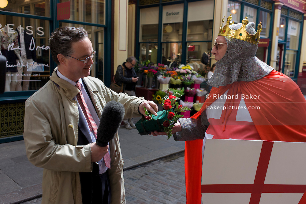 St George in full regalia hands out free red roses to Londoners in Leadenhall Market in the City of London, on England's national St George's Day the 23rd April,