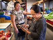 03 AUGUST 2019 - ST. PAUL, MINNESOTA: A woman checks her shopping list on her smart phone in the vegetable section of the Hmongtown Marketplace. Thousands of Hmong people, originally from the mountains of central Laos, settled in the Twin Cities in the late 1970s and early 1980s. Most were refugees displaced by the American war in Southeast Asia. According to the 2010 U.S. Census, there are now 66,000 ethnic Hmong in the Minneapolis-St. Paul area, making it the largest urban Hmong population in the world. There are two large Hmong markers in St. Paul. The Hmongtown Marketplace has are more than 125 shops, 11 restaurants, and a farmers' market in the summer. Hmong Village is newer and has more than 250 shops and 17 restaurants.    PHOTO BY JACK KURTZ