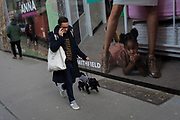 A man walks his dog past a large billboard, part of a series of portraits by photographer Lucy Alex Mac, that show pregnant women at West Smithfield, in the former Smithfield meat market that is awaiting future redevelopment, on 20th November 2019, at Smithfield in the City of London, England. As part of the Museum of London's plans to move into Smithfield's General Market Building, this photography show celebrates pregnant residents of Waltham Forest. The cost of the move is estimated to be in the region of £70 million and, if funding can be achieved, would be complete by 2021. There has been a market on this location since the Bartholomew Fair was established in 1133 by Augustinian friars.