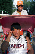October 2004 - Phnom Penh; Cambodia - Chhin Toeun (left); 24; or Hawaii to his friends; sits in a rickshaw to travel a few blocks across central Phnom Penh. After spending more than 7 years in prison; he was deported back to Cambodia. Previously a gang member in the US; he remains dressed like an American covered in tatoos and is seen as a foreigner to local Khmers even though he was born in Cambodia. After escaping the Khmer Rouge regime to the US as refugees; many young American Cambodians are being sent back to Cambodia never to return to the US again. A new policy in 2002 meant that any US-Cambodian who still had not applied for US citizenship and had been convicted of a felony would be deported back to Cambodia after living in the US all their life. Over 1; 400 convicted felons are proposed to be sent back in the next few years and naturally the re-adjustment to a life they don't know or understand is a difficult one. Photo Credit: Luke Duggleby