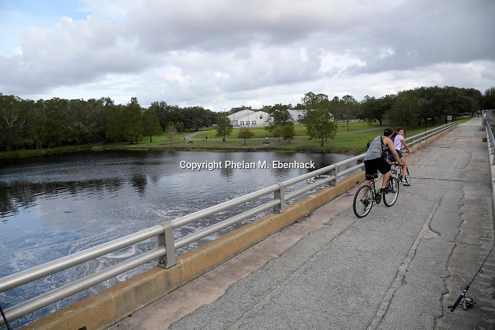 Bicyclists ride along a bridge over the Little Econlockhatchee River in Jay Blanchard Park Saturday, Oct. 21, 2017, in Orlando, Fla. (Photo by Phelan M. Ebenhack)