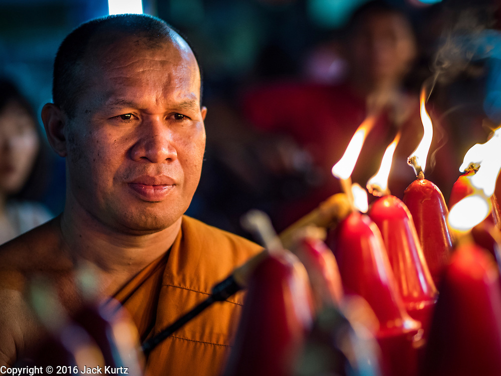 """07 FEBRUARY 2016 - BANGKOK, THAILAND: A Buddhist monk lights candles during a Chinese New Year ceremony at Wat Traimit in Bangkok's Chinatown neighborhood. Chinese New Year, also called Lunar New Year or Tet (in Vietnamese communities) starts Monday February 8. The coming year will be the """"Year of the Monkey."""" Thailand has the largest overseas Chinese population in the world; about 14 percent of Thais are of Chinese ancestry and some Chinese holidays, especially Chinese New Year, are widely celebrated in Thailand.        PHOTO BY JACK KURTZ"""