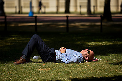 © Licensed to London News Pictures. 16/07/2019. LONDON, UK.  A man relaxes in the sunshine in St. James's Park.  Temperatures are forecast to rise to 26C.  Photo credit: Stephen Chung/LNP