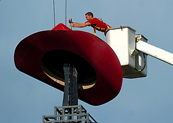 Chris Anthony of Hargis Electric begins screwing in a eye bold in the top rim of the 1,400 pound red cowboy hat that sits atop the Eiffile Tower in Paris, Texas Tuesday, April 18, 2006.  The eight year old Paris landmark is being taken down for cleaning and a fresh coat of paint.