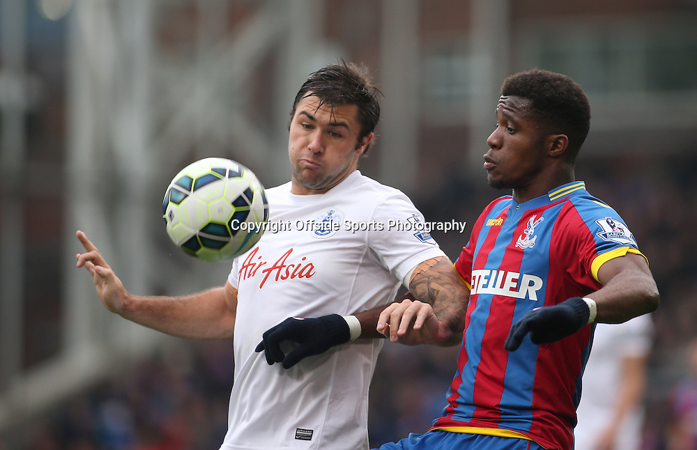 14 March 2015 - Barclays Premier League - Crystal Palace v Queens Park Rangers - Wilfried Zaha of Palace and Charlie Austin of QPR battle for possession.<br /> <br /> Photo: Ryan Smyth/Offside