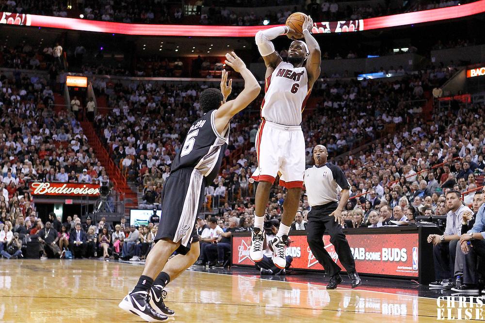 17 January 2012: Miami Heat small forward LeBron James (6) takes a three-points jumpshot over San Antonio Spurs guard Cory Joseph (5) during the Miami Heat 120-98 victory over the San Antonio Spurs at the AmericanAirlines Arena, Miami, Florida, USA.
