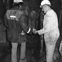 Banksman collecting checks from miners going underground at Markham Main Armthorpe Colliery. National Coal Board, Doncaster Area 21/06/1983.