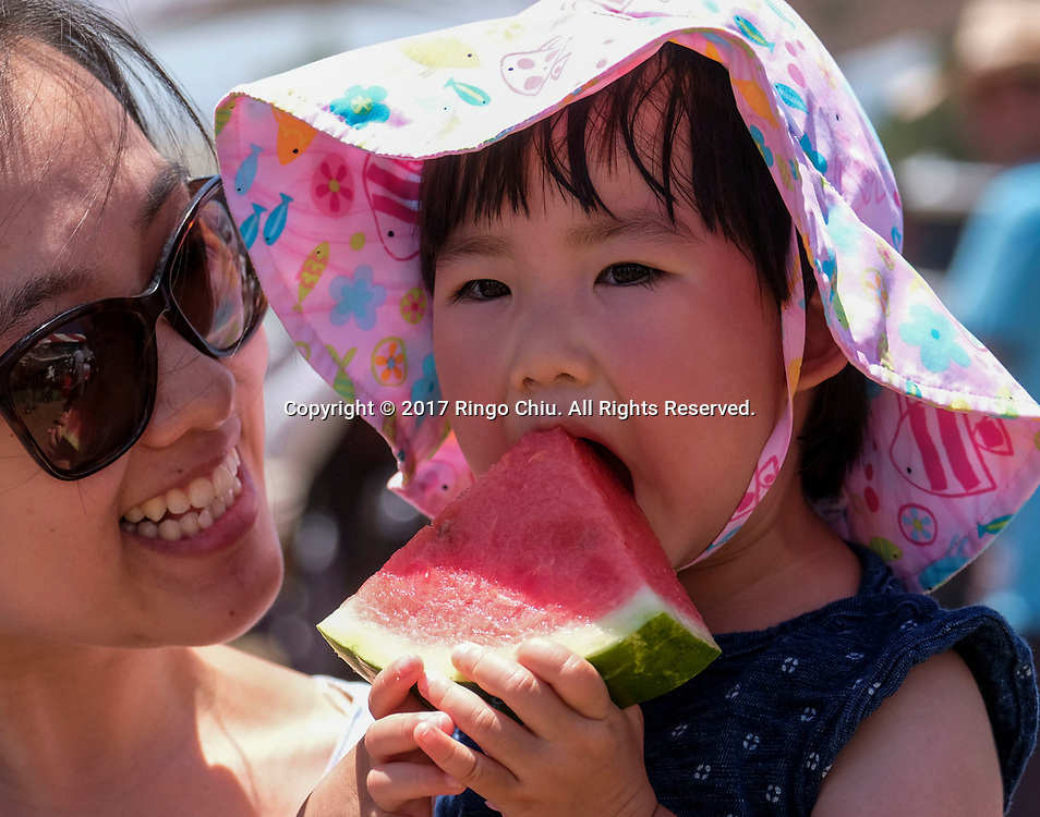 新华社照片,洛杉矶,2017年7月30日<br />     (国际)(1)第五十五届加州西瓜节<br />     7月29日,小孩子品尝鲜甜西瓜。<br />     在美国洛杉矶,大批民众出席了&quot;第五十五届加州西瓜节&quot;。<br />     新华社发(赵汉荣摄)<br /> A baby enjoys the watermelon at the 55th Annual California Watermelon Festival in Los Angeles, the United States, Saturday, July 29, 2017. (Xinhua/Zhao Hanrong)