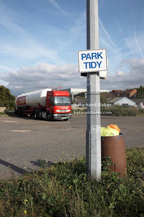 Sign on lamp post telling HGV drivers to Park Tidy in an overnight lorry park on the A126 in industrial Grays, Thames Gateway