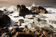 Waves Crashing against the rocky granite coast at Cape Cornwall, St Just, Cornwall. The Brisons offshore stacks can be seen in the distance. Years of relentless attack by the Atlantic Ocean has rounded much of the hard granite stone shoreline.