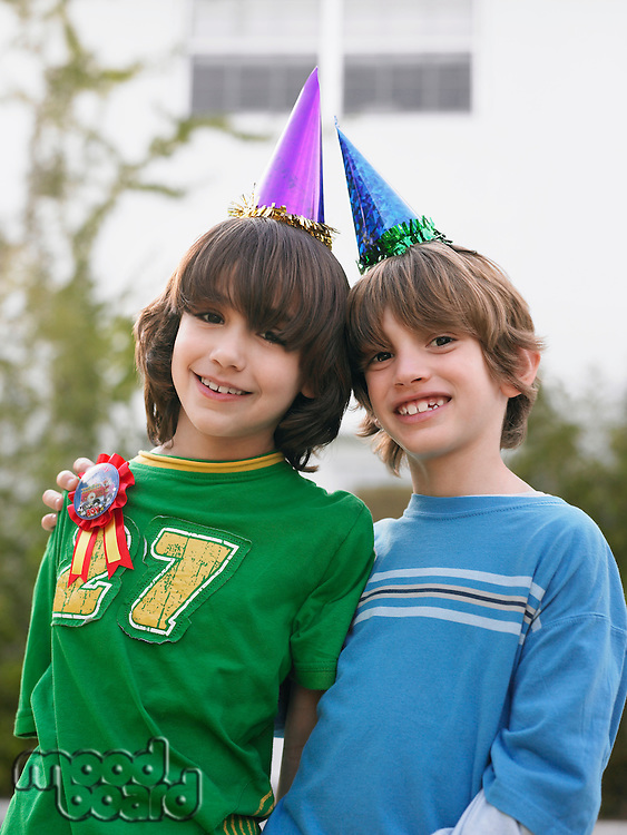 Portrait of two boys (10-12) in party hats close-up