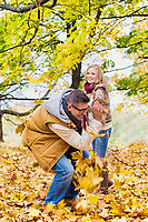 Portrait of mature couple playing with maple leaves in park