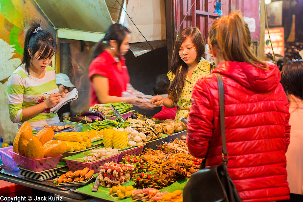 01 APRIL 2012 - HANOI, VIETNAM:   People at street side food stalls in the Old Quarter of Hanoi, Vietnam.     PHOTO BY JACK KURTZ