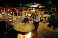 A man stirs a cauldron of corn soup over a roaring wood fire in an outdoor restaurant  in the small farm town of Cumbre,  in the highlands outside of Cali, Colombia.