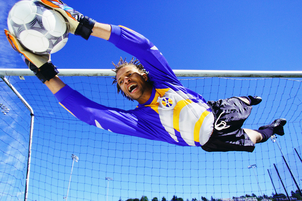 A mixed race soccer goalie diving to make a save.