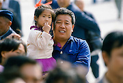 Chinese father and child among the crowds in Tiananmen Square in Peking, now Beijing, China in the 1980s