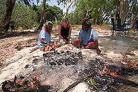 A visitor chats with local aboriginal Wik women Dawn Koondumbin and Vera Ngallematta beside a pit fire cooking freshly caught fish in the Aurukun Wetlands, remote Cape York, far northern Queensland, Australia.