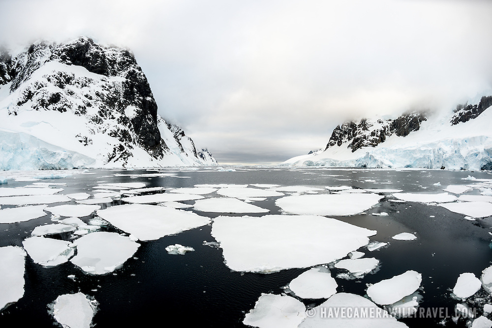 Scenic shot of the sea ice, calm waters, and towering cliffs of the Lemaire Channel in Antarctica.
