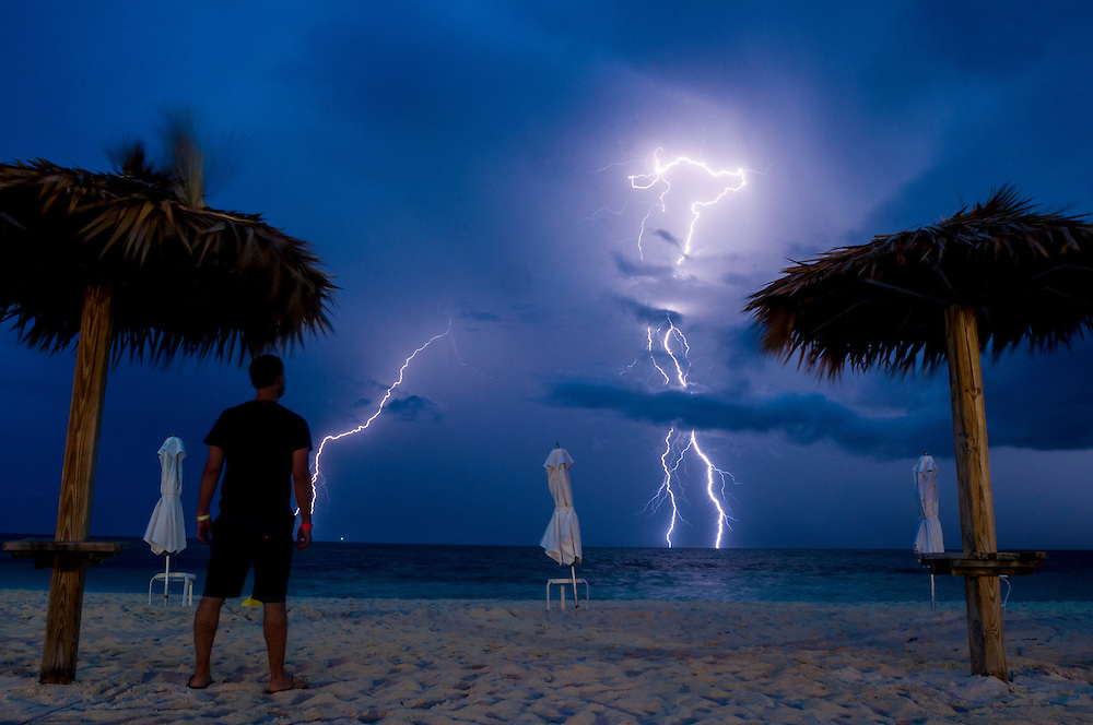 Self-portrait taken as a long exposure on a beach on Freeport, Grand Bahama. A massive lightning storm passed by, just off the beach.