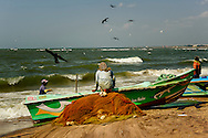 A man sitting on his fish net and relaxing at the Negombo fish market. This fish market is the second largest fish market in Sri Lanka. It is situated near the Old Dutch Fort Gate and held every day except Sundays
