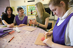 Day Service Care Assistants working with a Group of Day Service users with learning disabilities in an arts and crafts session,