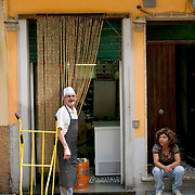 An Italian butcher wearing a butchers white hat and pin stripped apron laughs at a woman sitting outside the back of the butcher's  shop in the village of Corniglia on the coastline located in nothern Italy's Riveria located in Cinque Terre region in western Italy. The woman is smoking a cigarette and staring at the butcher.