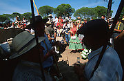 """Dancing Sevillanas, the merry pilgrims stop for a lunch break. The pilgrim route of the Hermandade de Sanlucar de Barrameda from Sanlucar across the Parque Donana to El Rocio, Huelva Province, Andalusia, Spain...El Rocio follows on from Semana Santa - Easter week and the various spring ferias, of which Seville's Feria de Abril (April) is the biggest. The processions to the (Hermitage) Hermita de El Rocío, at Pentecost, is the most famous (Romeria) pilgrimage in the Andalusian region, attracting nearly a million people from across Andalusia, Spain and the world. The cult started off in the 13th century when a statue of the virgin Mary was apparently found in a tree trunk in the Donana Park. What was first a local devotion at Pentecost by local pilgrim brotherhoods """"hermandades"""" became by the 19th century into dozens of fraternities developed from such as Cadiz, Selville and Huelva. Some walk for several days, others travel with oxen drawn wagons or on horseback, with traction engines and all terrain vehicles, camping along the trail they take. They wear Andalusian costumes, tight breeches, boots, short jackets and frilly flamenco skirts. Many festivities, flamenco dance, laments, songs and music are combined with religious prayers. Devout pilgrims walk as a penance, keeping vows of silence. An emblem of the immaculate conception (sin peche) is carried. On the Pentecost after the stroke of midnight on the whit Sunday the virgin Mary is carried from the church through the streets of El Rocio by each hermandade to visit each brotherhood's shrine."""