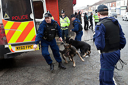 © licensed to London News Pictures. Heywood, UK  03/03/2012. Police with dogs give chase to about two dozen people following a National Front demonstration in Heywood, Greater Manchester The National Front hold a demonstration in Heywood, Greater Manchester. They protested against an alleged paedophile ring that had been operating in the area. There is currently a case being tried at Liverpool Crown Court in relation to the allegations. Last Thursday (23rd February) a protest organised in the town in relation to the same story resulted in Asian business being attacked by an angry mob. Photo credit should read Joel Goodman/LNP