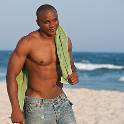 Shirtless young african american man Walking on the beach carrying a green towel