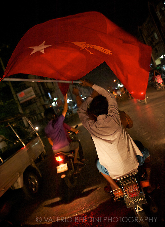 A motorbike passenger waves a NLD flag at night in Mandalay. Myanmar. 2012