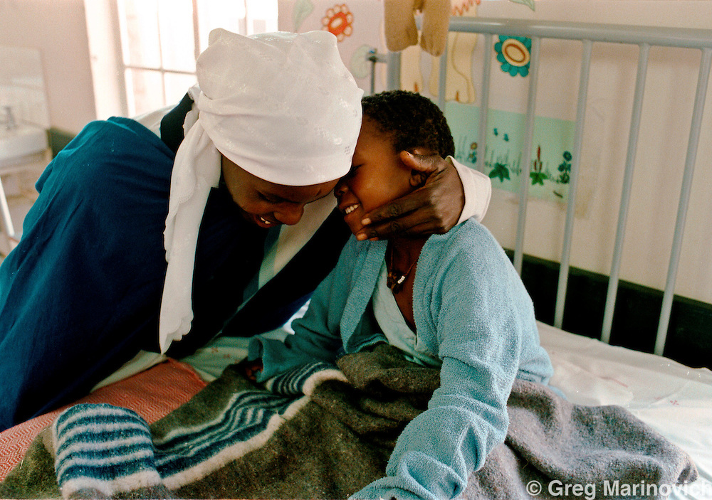 IPMG0103 South Africa, Tugela Ferry 2000: .A mother arrives and greets her child in the Aids ward at Tugela Ferry Hospital, KwaZulu Natal, South Africa, Aug 2000. Southern Africa has the highest per capita Aids sufferers, and KwaZulu Natal is the worst hit province. .Photograph by Greg Marinovich/South Photographs