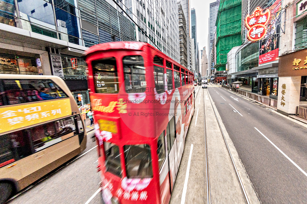 Historic double decker trams travel Des Voeux Road in the central district of Hong Kong.