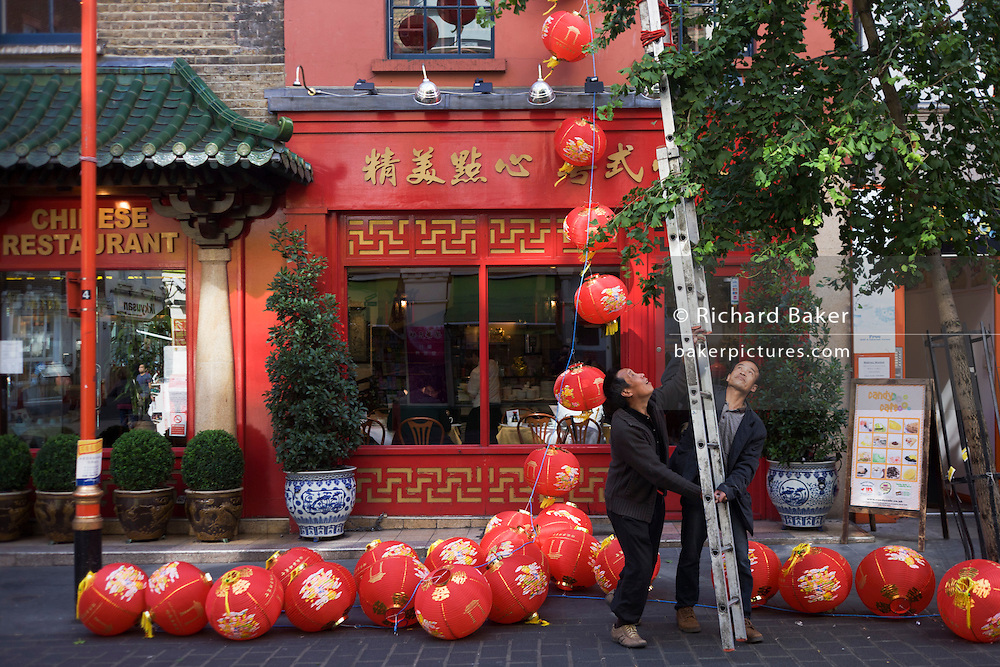 """Preparations in London's Chinatown for the mid-Autumn (also Lantern or Moon) Festival where paper lanterns are to hang. The Mid-Autumn Festival, also known as the Moon Festival or Zhongqiu Festival is a popular harvest festival celebrated by Chinese, Korean, and Vietnamese people, dating back over 3,000 years to moon worship in China's Shang Dynasty. It was first called Zhongqiu Jie (literally """"Mid-Autumn Festival"""") in the Zhou Dynasty. In Malaysia, Singapore, and the Philippines, it is also sometimes referred to as the Lantern Festival or Mooncake Festival. The Mid-Autumn Festival is held on the 15th day of the eighth month in the Chinese calendar, which is in September or early October in the Gregorian calendar. It is a date that parallels the autumnal equinox of the solar calendar, when the moon is at its fullest and roundest."""