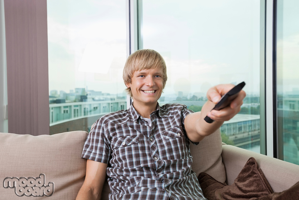 Smiling mid-adult man watching television on sofa at home