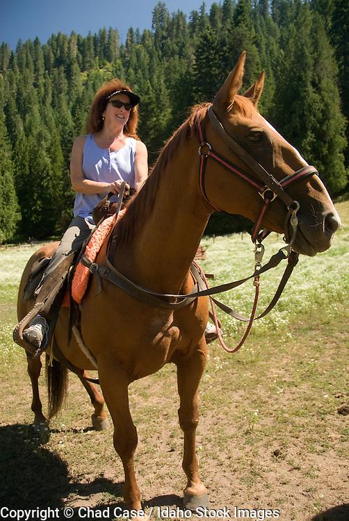 Idaho. Woman enjoys a horseback ride near Selway River, Nez Perce National Forest. MR