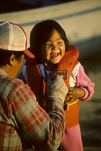 Northwest Territories, known as Nunuvat, Canada. John Tatty, Inuit guide, zips daughter Mary's life vest. Wager Bay.