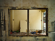 18 JULY 2017 - BANGKOK, THAILAND: Looking through an empty window frame into a home on Soi 27 off of Sathu Pradit in Bangkok. The area was a working class neighborhood of two storey shophouses. Most of the homes in the were occupied by Thais of Chinese heritage. The owner of the land sold the land to a developer who plans to build a condominium tower on the site. The residents left in early July and the shophouses will be torn down in coming weeks.       PHOTO BY JACK KURTZ