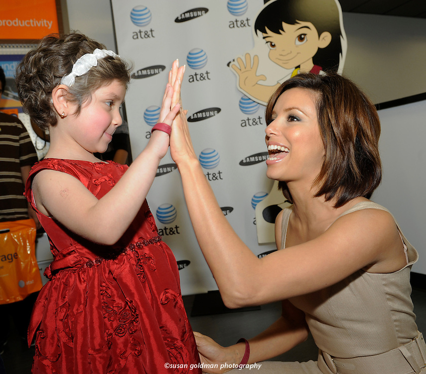 PADRES Contra El Cancer national spokeswoman Eva Longoria Parker, right, high fives with Alondra Mariscal, 5, in treatment for leukemia, following a check presentation of $200,000 from AT&T to PADRES, in Burbank, Calif. The donation to PADRES is the result of AT&T's third annual campaign, which raises money to support families coping with the devastating effects of childhood cancer. Photo/AT&T, Susan Goldman.