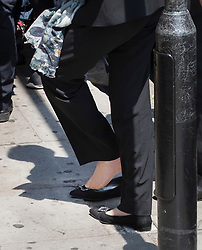 © Licensed to London News Pictures. 19/06/2017. London, UK. Prime Minister Theresa May briefly regains her shoe on the pavement outside Finsbury Park Mosque after tripping and losing it on arrival. Earlier a van ploughed into a crowd near Finsbury Park Mosque, as they finished taraweeh, Ramadan evening prayers. One person has been killed and 10 people are injured. Photo credit: Peter Macdiarmid/LNP