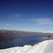 A Skier on top of Mount Albert on Minaret Station, Wanaka, with Lake Wanaka in the background. Wanaka, New Zealand. 31st July 2011