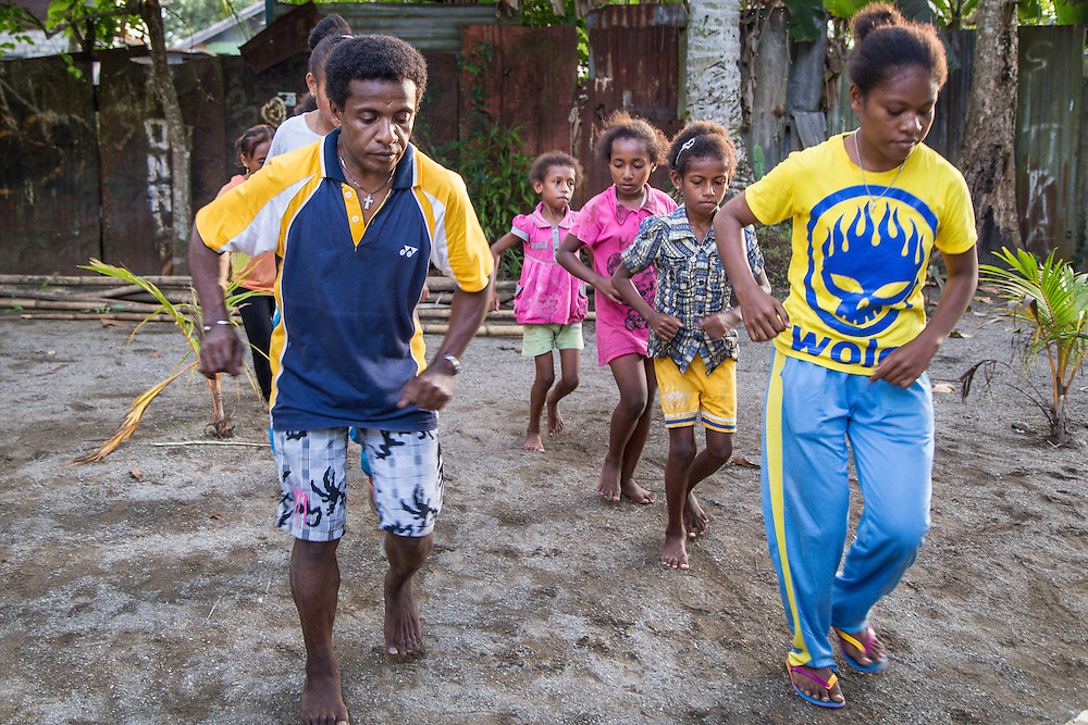 Yosua teaches a new dance routine to a group of neighborhood kids.