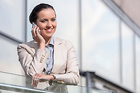 Happy young businesswoman using cell phone at office railing
