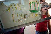 27 JUNE 2009 -- PHOENIX, AZ: KENDALL BRAUER, a student from Scottsdale, AZ, holds her sign up to the window after she was locked out of the state capitol during a march at the Arizona state capitol Saturday. Arizona has the second worst state budget deficit in the country (only California's is worst) and the Republican controlled legislature is threatening to balance the budget by making massive cuts in social and education spending while cutting taxes. Small numbers of public school teachers and parents of public school students have been marching on the capitol almost every day of the week but Saturday's march, with well over 500 people was the largest of session. The legislature and Gov. Jan Brewer, also a Republican, are deadlocked in negotiations and the Governor has threatened to shut down state government on July 1 if there is no budget. Republican leaders in the legislature are threatening to present the Governor with a budget, without input from the Governor's office, at midnight on June 30, forcing her to sign the budget to keep the state open.  Photo by Jack Kurtz